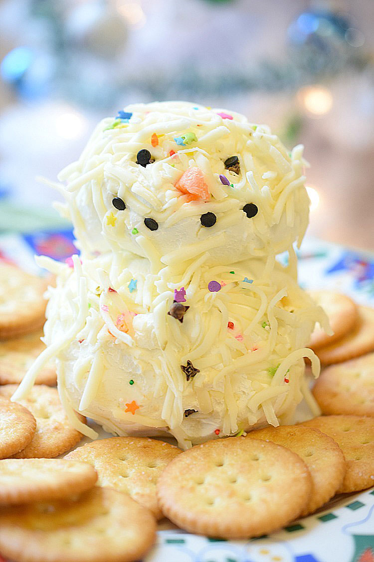 Easy holiday snowman cheese ball recipe with chipotle pepper and pepper jack cheese. Surrounded by Ritz crackers