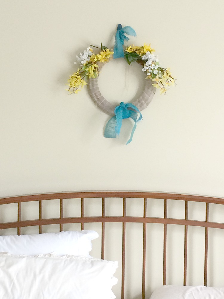 Faux forsythia wreath over bed in master bedroom