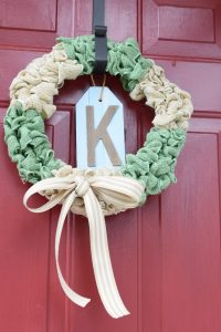 white and green burlap bubble wreath on a red front door
