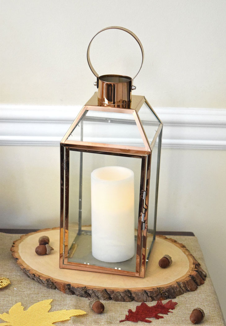 fall lantern on a natural wood slice on a console table