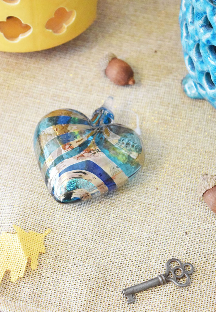 glass heart ornament, antique key, burlap leaves and craft acorns on a console table