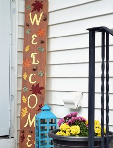 Fall porch welcome sign, lantern and mums on a fall front porch