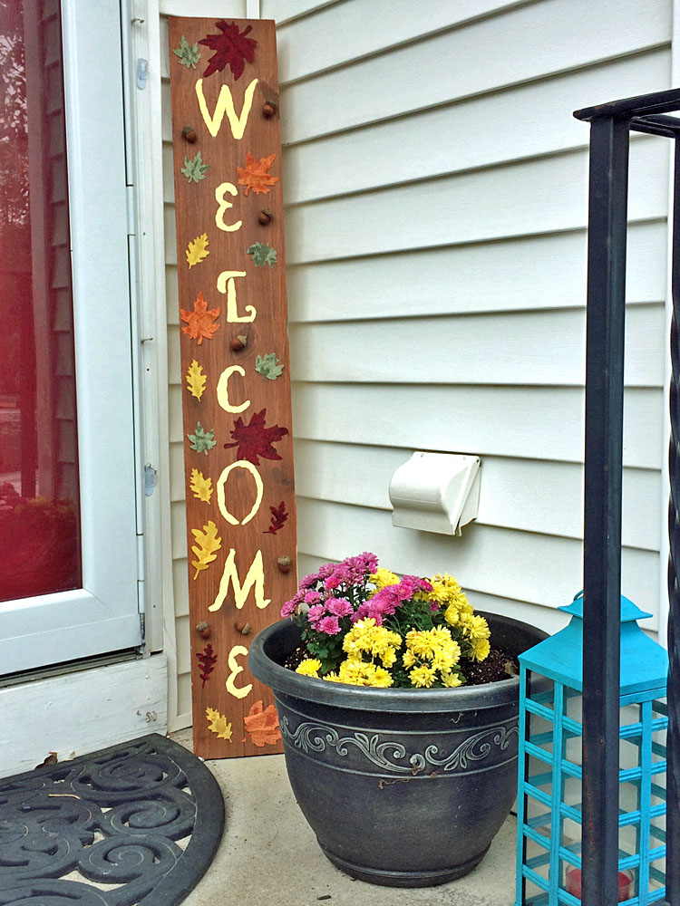 Fall porch decor with a DIY welcome sign, lantern and mums