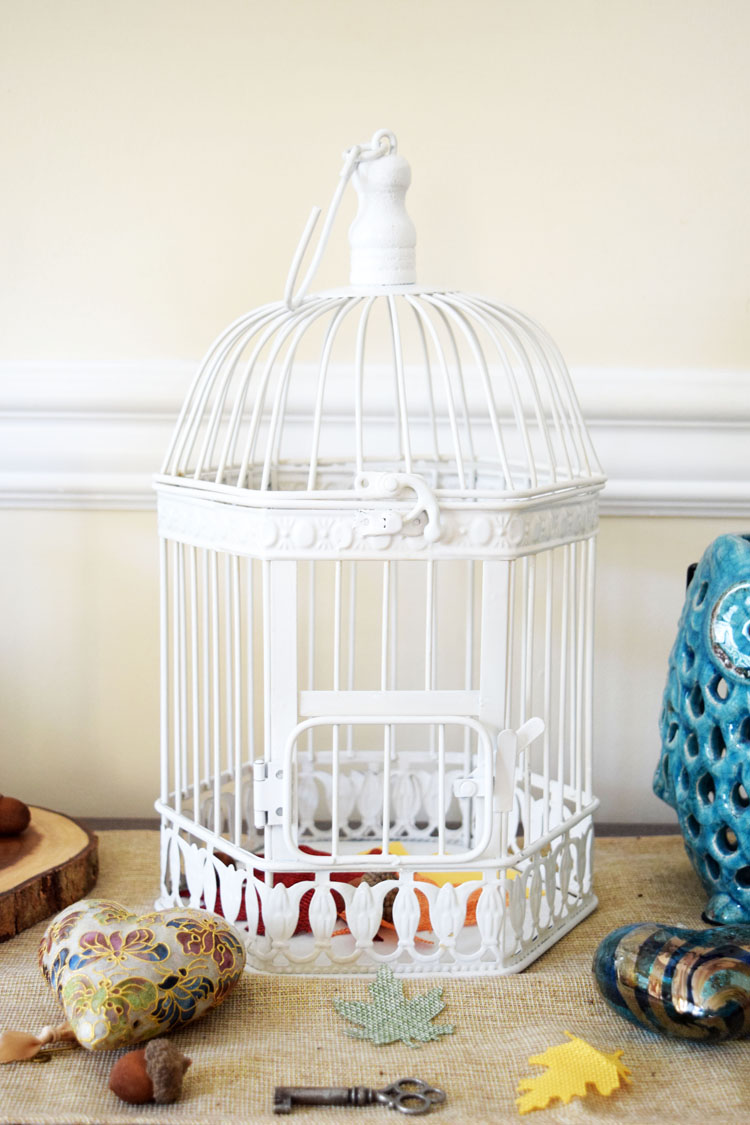 white metal birdcage on Oriental Trading on a fall console table