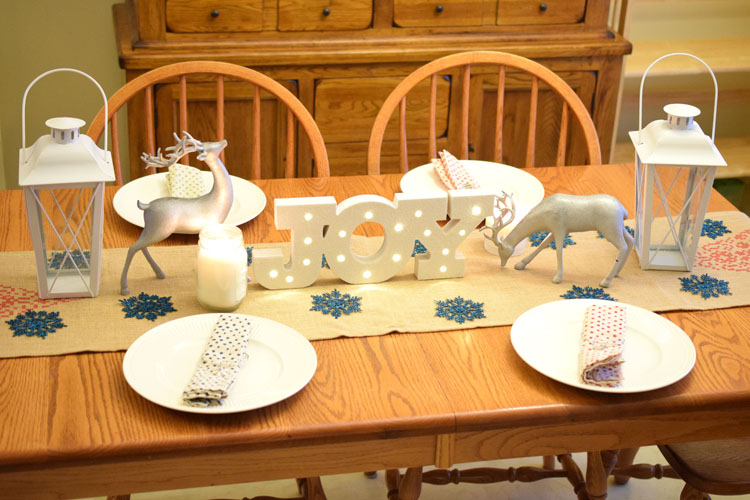 Christmas farmhouse table with burlap table runner, silver reindeer, candles and lanterns, plus a lighted Joy marquee sign