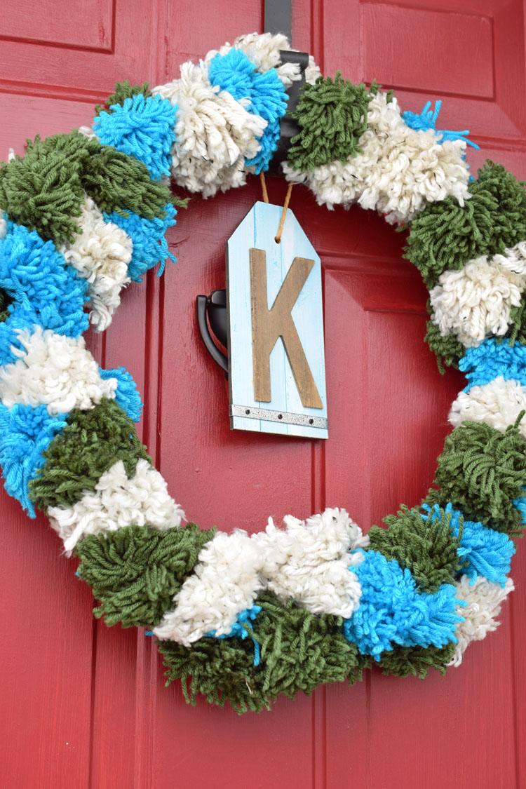 white, green and blue pom pom wreath for Christmas