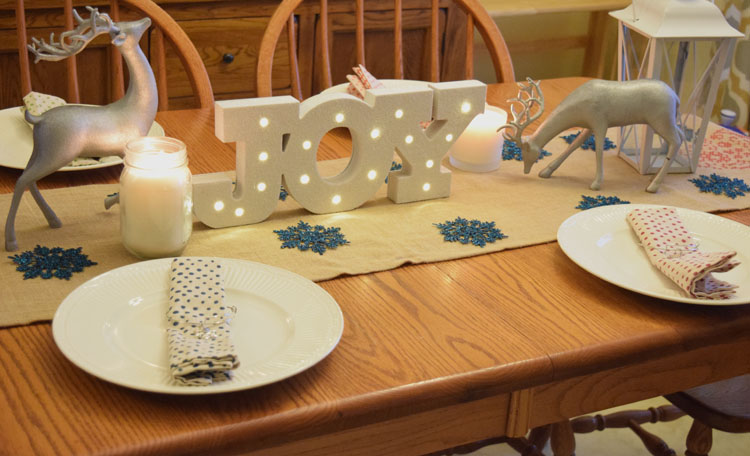 Christmas holiday table with silver reindeer, burlap table runner and lighted Joy marquee sign