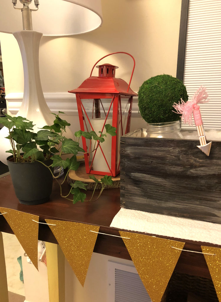 Console table with a red lantern, planter box with mason jars and moss and a gold pennant banner