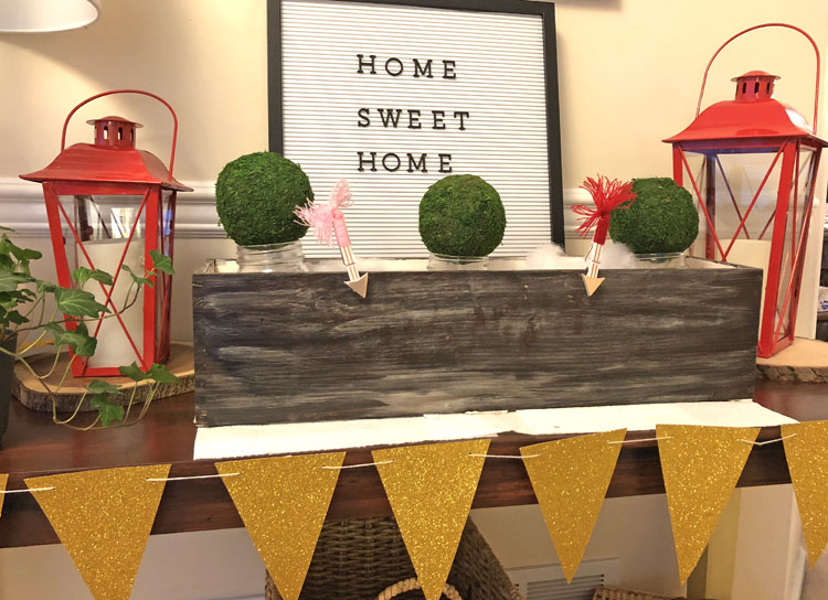 Console table decorated for Valentine's Day with a gold banner, red lanterns, planter box, bell jars filled with moss and a letter board.