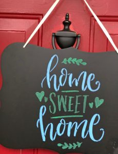 A beautiful Home Sweet Home chalkboard sign made for a front door with some liquid chalk markers and a stencil from Stencil Revolution
