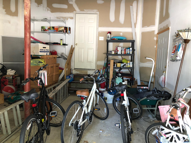 a messy garage with bikes and other odds and ends that could use a good storage system and a makeover