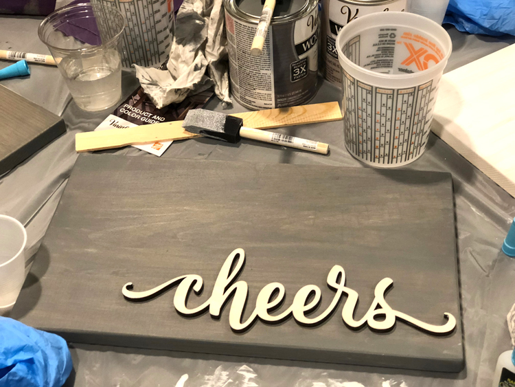 DIY cheers sign made by staining a plank of wood and a word cut-out with Rustoleum quick drying stain