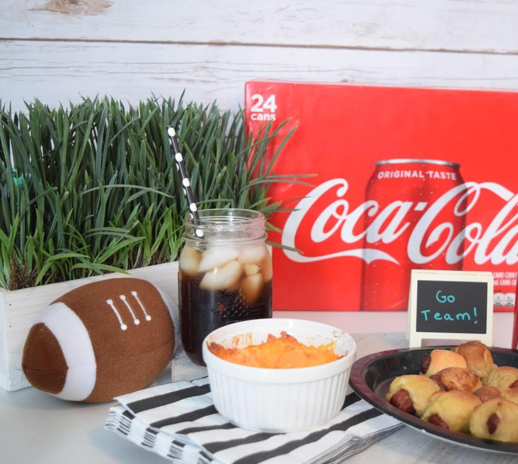 box of 24 cans of Coca-Cola at a fun football watch party with mini pretzel dogs and pimento cheese dip