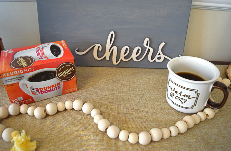 cup of coffee on a coffee table in front of a cheers sign and behind a wooden bead garland