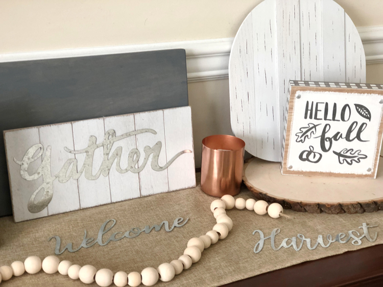 console table with hello fall and gather signs, wood round, copper candle and natural wood bead garland on a burlap table runner