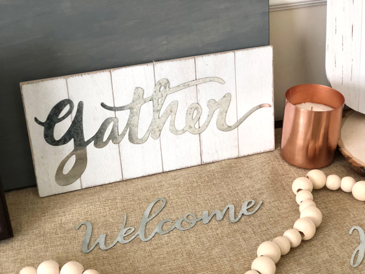 metal welcome word, gather farmhouse-style sign, copper candle and natural wood bead garland on a fall console table