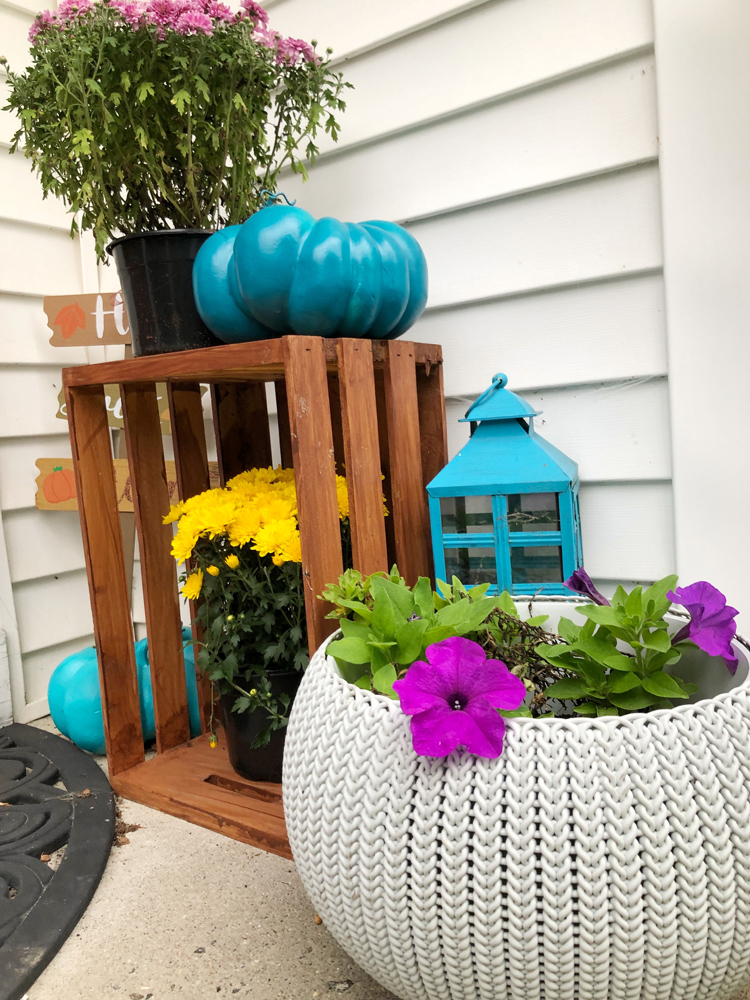 small front porch with turquoise pumpkin, lantern, mums, petunia and wood crate