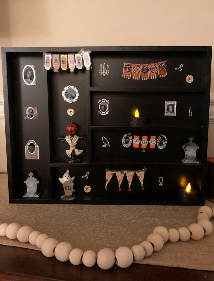 This easy to make and inexpensive DIY Halloween shadow box and display curio case looks great on a console table.