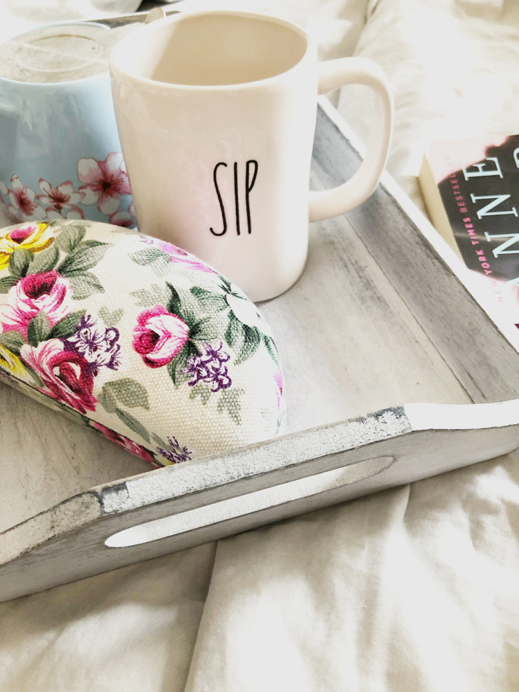 Gray breakfast tray with floral eyeglass case, Rae Dunn sip mug and mini blue teapot on a set of cotton gray sheets