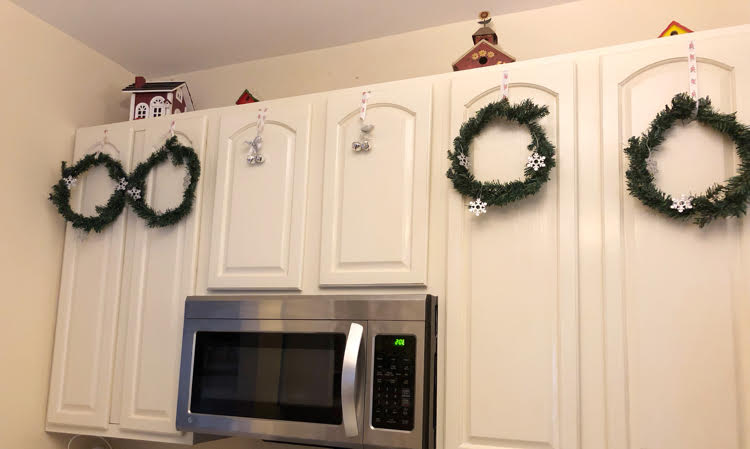 Faux Christmas wreaths hung on white kitchen cabinets with ribbon