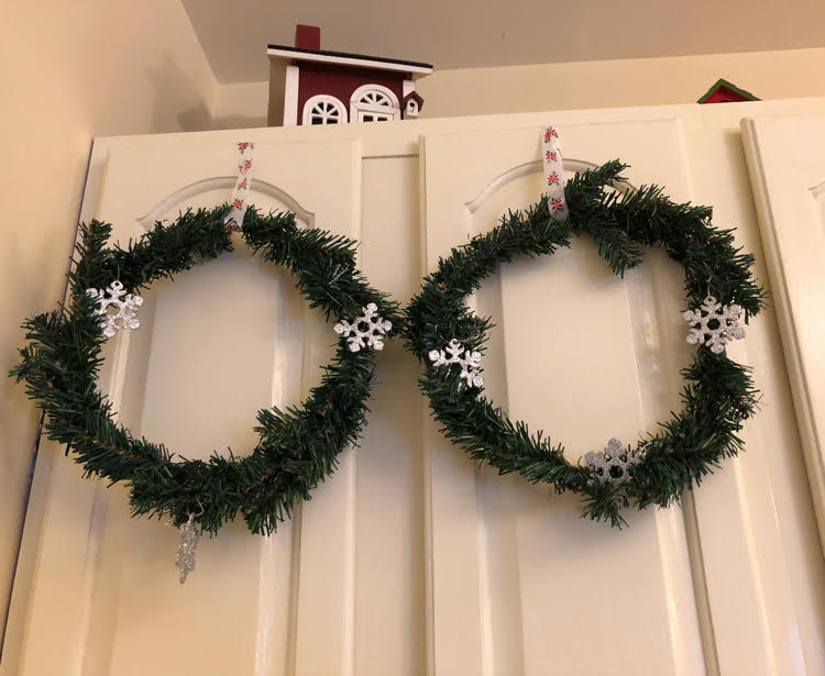 Dollar store wreaths hung on white kitchen cabinets