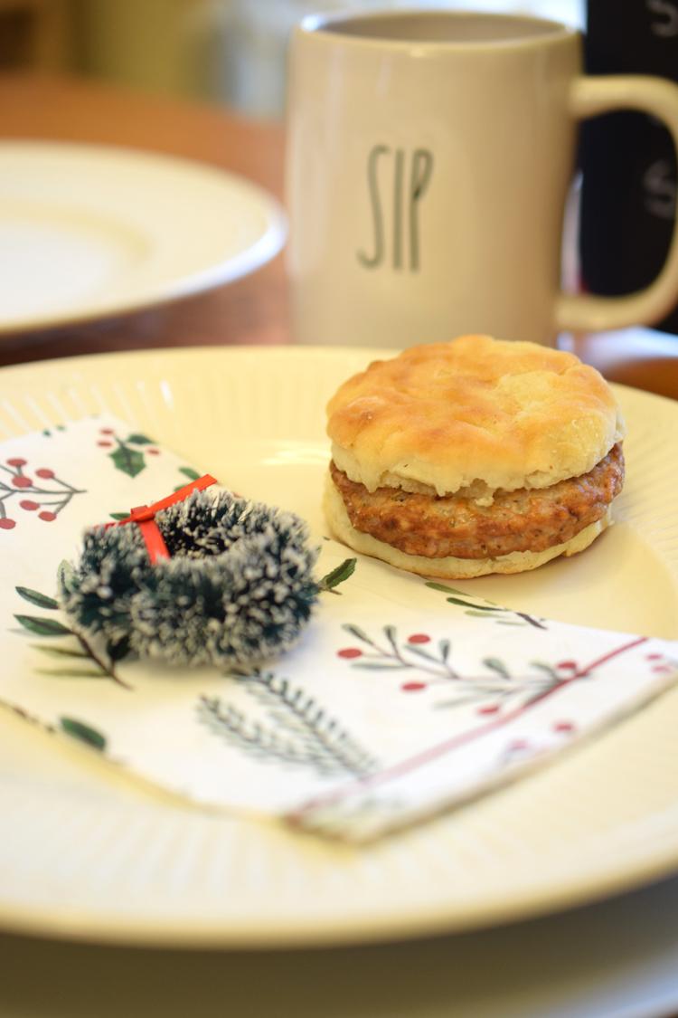 Christmas holiday table set with Rae Dunn mug, Christmas napkin, breakfast sandwich and miniature wreath