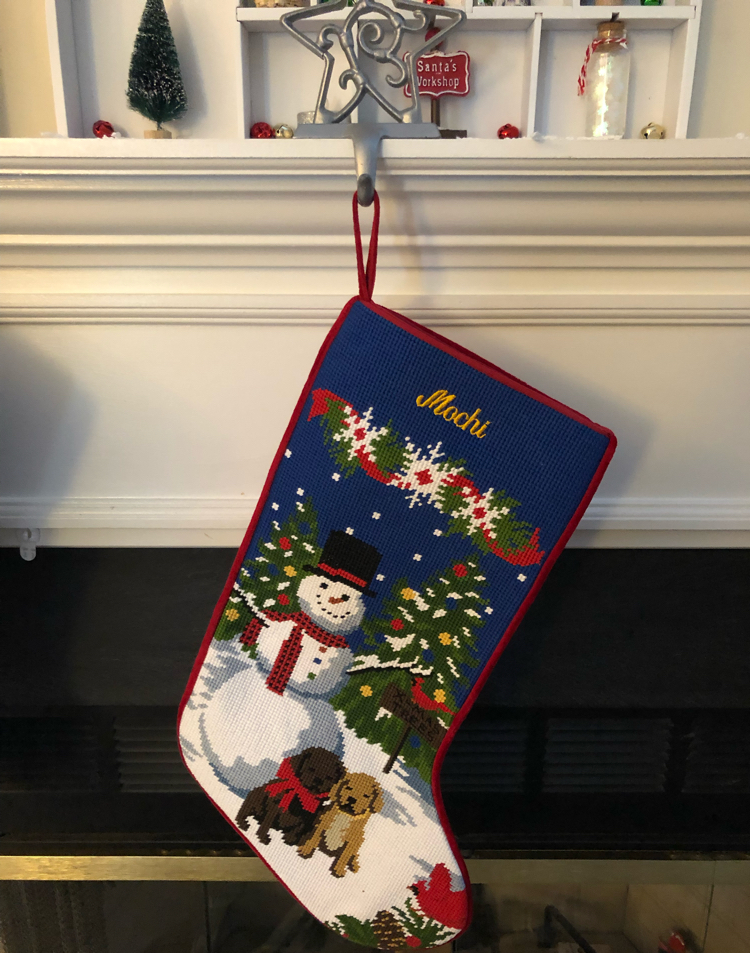 blue needlepoint stocking with two puppies and a snowman
