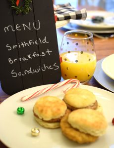 Adorable breakfast table with chalkboard menu, breakfast sandwiches and juice