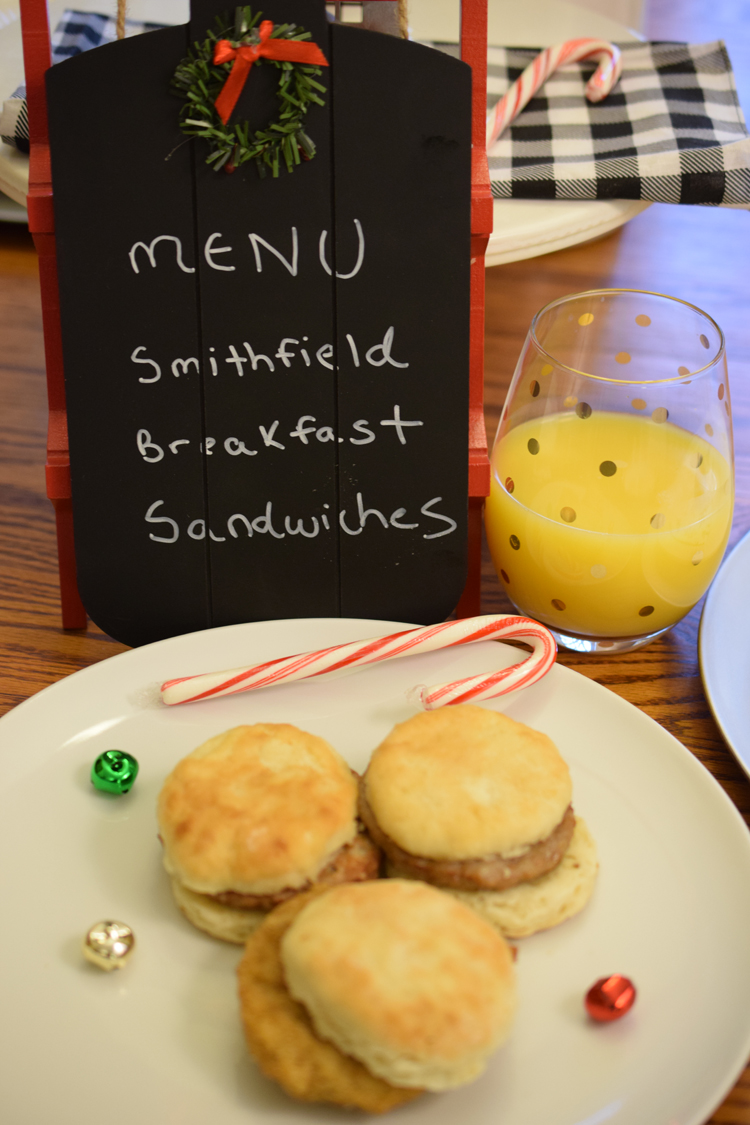 A Christmas holiday table set with juice, breakfast sandwiches and a cute chalkboard menu