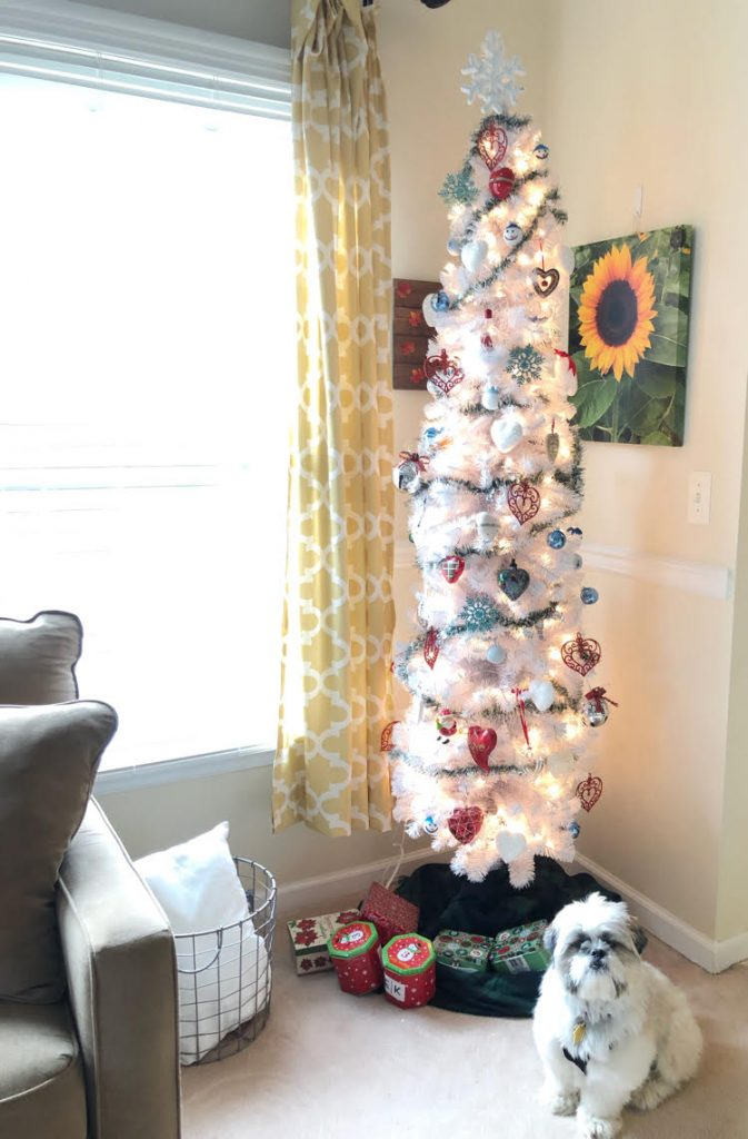 A white Christmas tree with colorful ornaments and a white Shih Tzu puppy