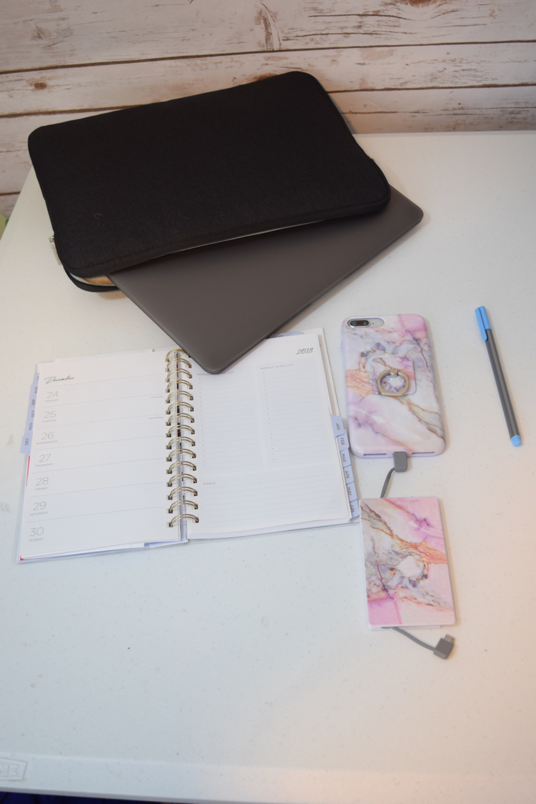 MacBook Air with laptop case, iPhone with case and portable phone bank charger, plus planner