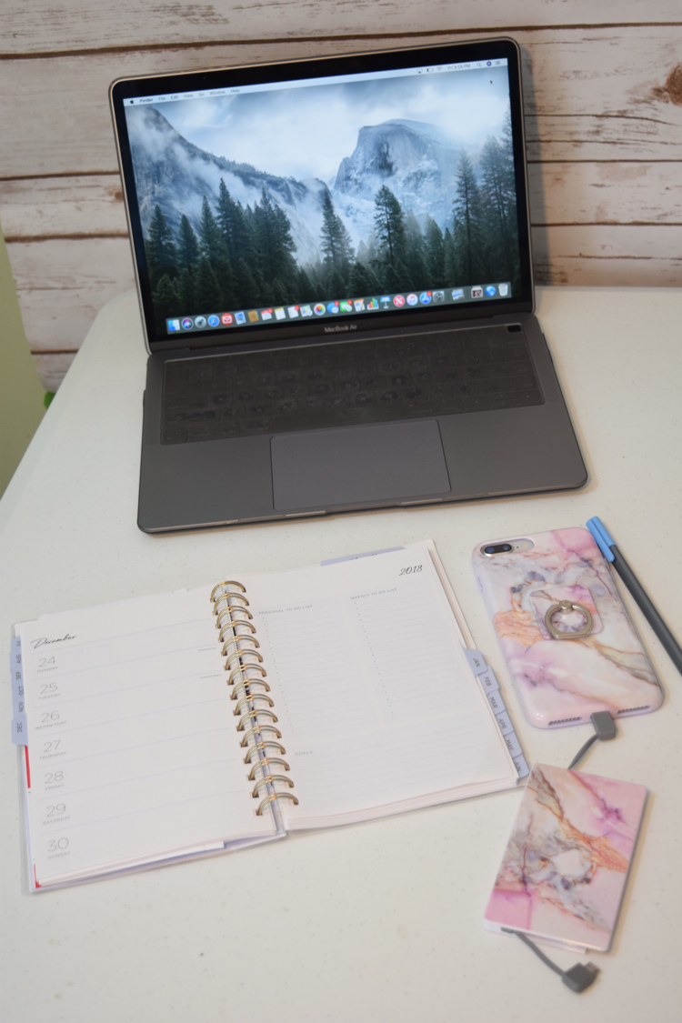 MacBook Air with iPhone 8 Plus with a marble phone case and portable phone bank charger