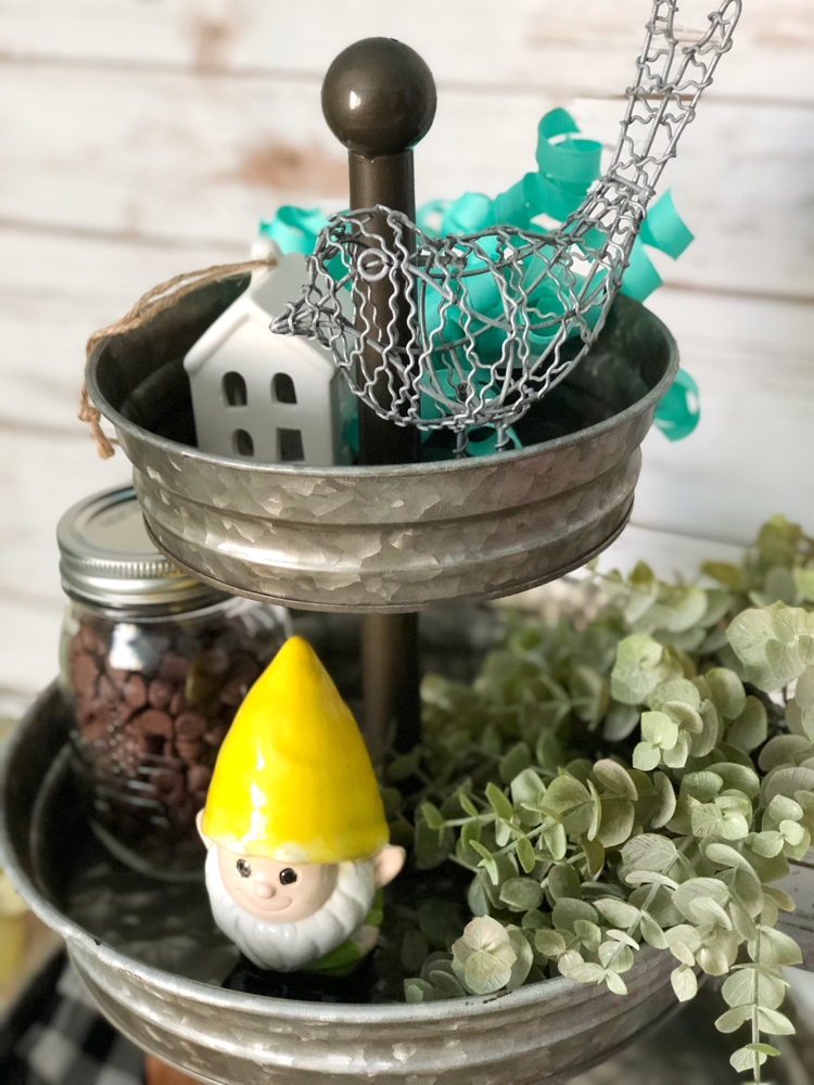 A galvanized metal tiered tray with miniature birds and houses, a garden gnome, faux greenery and a buffalo plaid napkin.