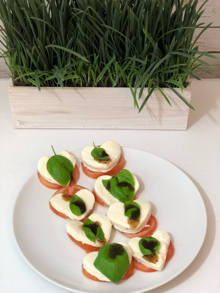 A Valentine's Day caprese heart salad made with fresh mozzarella, tomatoes, basil leaves and balsamic dressing.