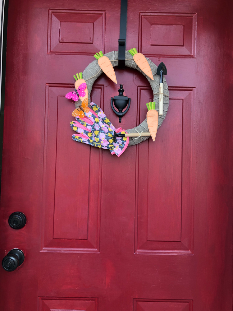 This spring gardening wreath was easy to make with burlap ribbon and inexpensive items from Target and the dollar store