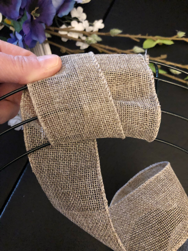 A floral wreath can be made easily by wrapping a metal wreath form with burlap wire ribbon