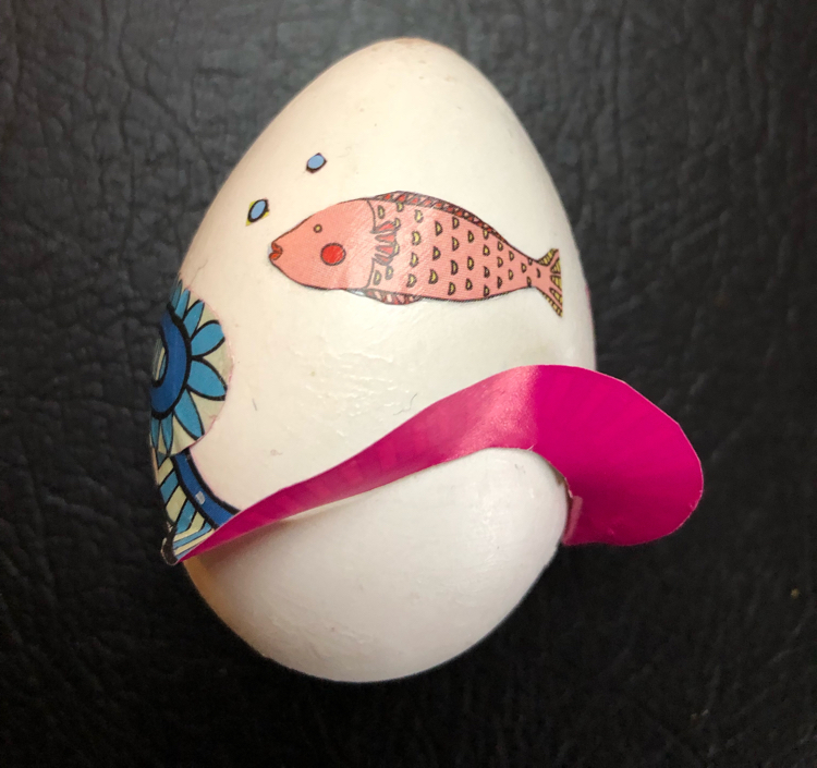 A craft Easter egg decoupaged with fish origami paper
