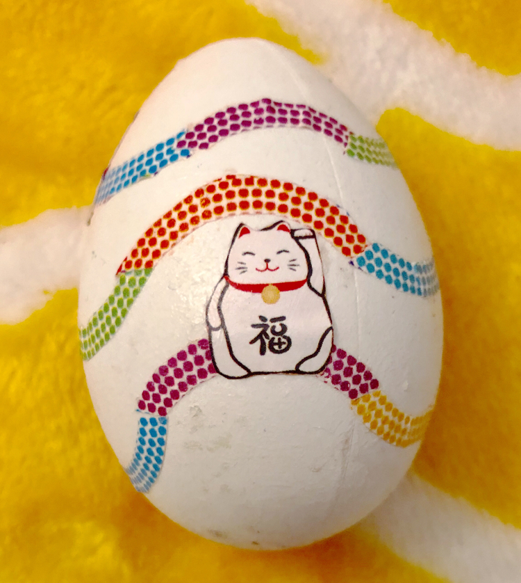 A craft Easter egg decoupaged with maneki-neko origami paper.