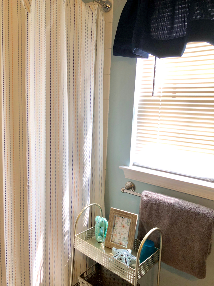 white shower curtain and blue curtain valance