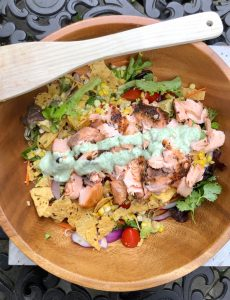 Green salad with salmon and avocado and a creamy cilantro dressing. Plus, it's topped with crushed tortilla chips.
