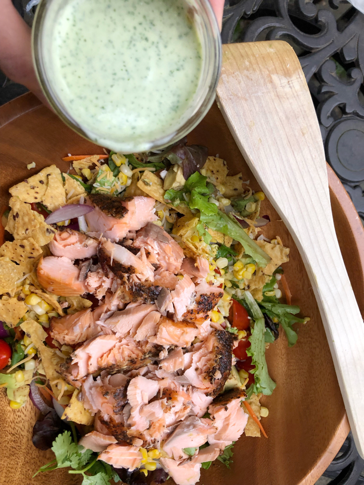 A fresh green salad with Atlantic salmon, avocado, corn and a homemade cilantro lime dressing.