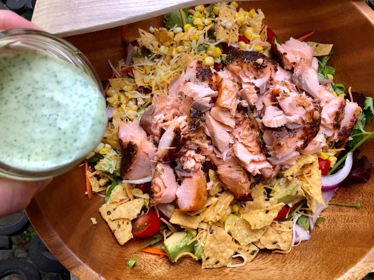green salad with salmon, avocado and tomato, topped with a creamy cilantro lime dressing