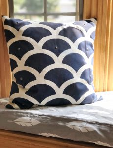 A DIY box cushion with homemade piping. Also shown is a DIY stenciled pillow