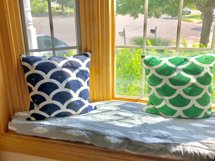 DIY window seat cushion in a bay window with colorful pillows