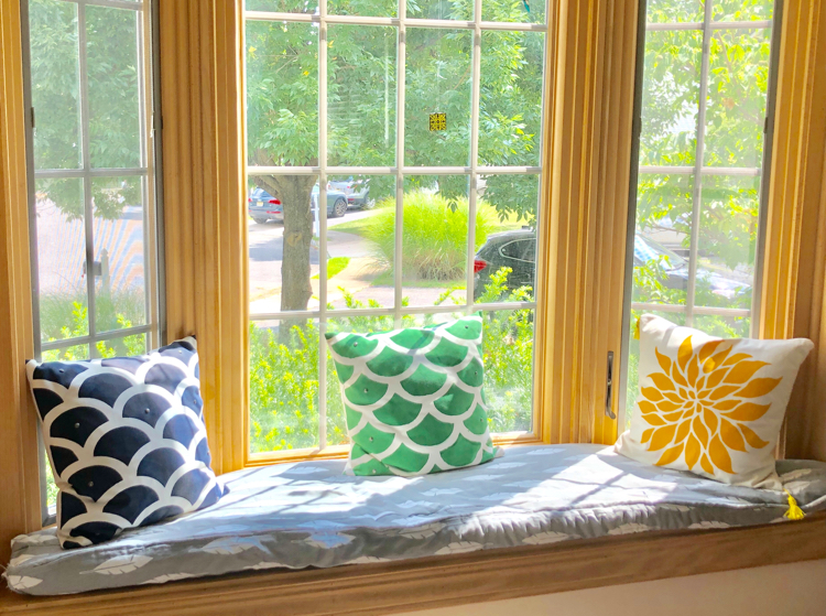 A window seat with a DIY boxed cushion with piping. Also shown are DIY stenciled pillows.