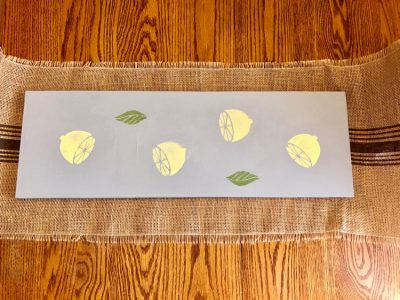 A DIY wooden table runner stenciled with lemons using DecoArt Americana Chalky Finish Paints