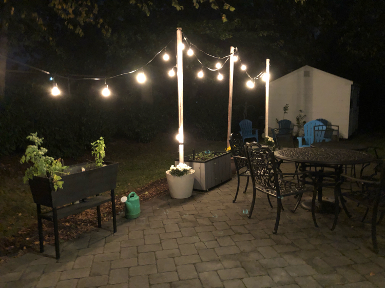 A paver patio lit at night with DIY planter string light poles and string lights.