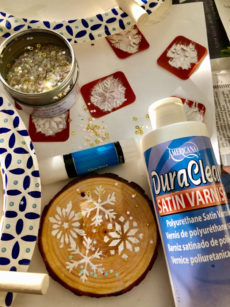 How to make a winter snowflake wood slice ornament with stencils, paint and confetti glitter.