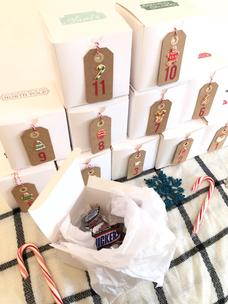 A DIY Christmas advent calendar made out of white gift boxes. One of the boxes is filled with candy.