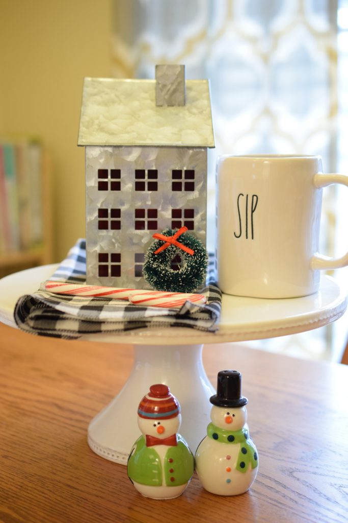 a sweet and simple Christmas tablescape with a cake stand, snowman salt and pepper shakers and a mini metal house.